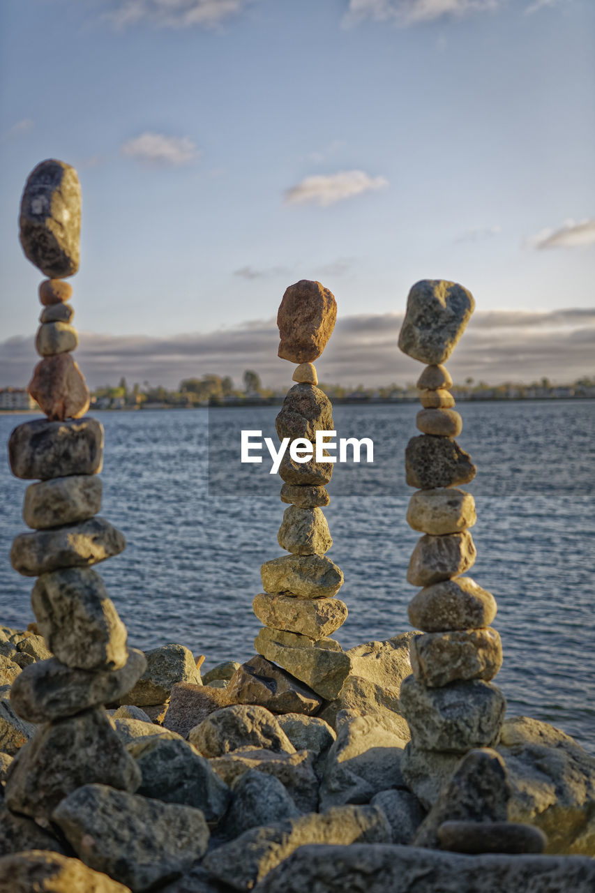 sky, solid, rock, water, nature, rock - object, sea, focus on foreground, stone - object, beach, land, no people, beauty in nature, balance, tranquility, stack, day, tranquil scene, zen-like, outdoors, pebble