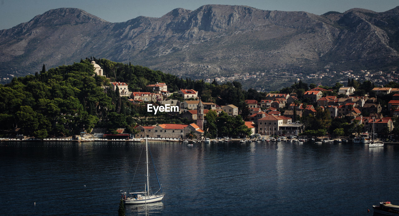 architecture, mountain, nautical vessel, building exterior, built structure, water, transportation, city, mode of transportation, building, sea, nature, no people, waterfront, residential district, mountain range, day, town, outdoors, cityscape, sailboat, townscape, yacht
