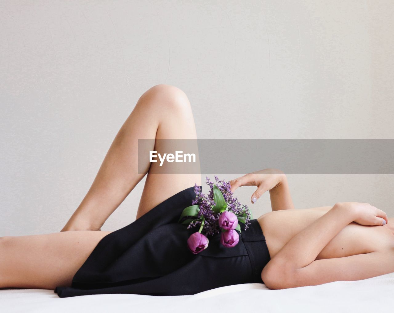 Midsection of topless woman lying on bed with flowers against beige background