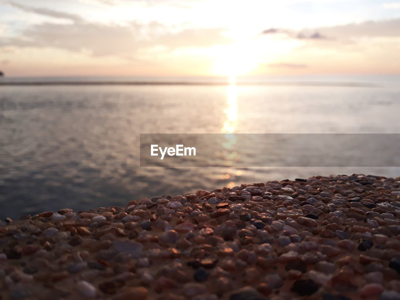 sky, water, sea, sunset, beach, scenics - nature, beauty in nature, horizon, tranquil scene, tranquility, horizon over water, rock, stone - object, nature, solid, cloud - sky, land, sun, selective focus, pebble, no people, outdoors, surface level