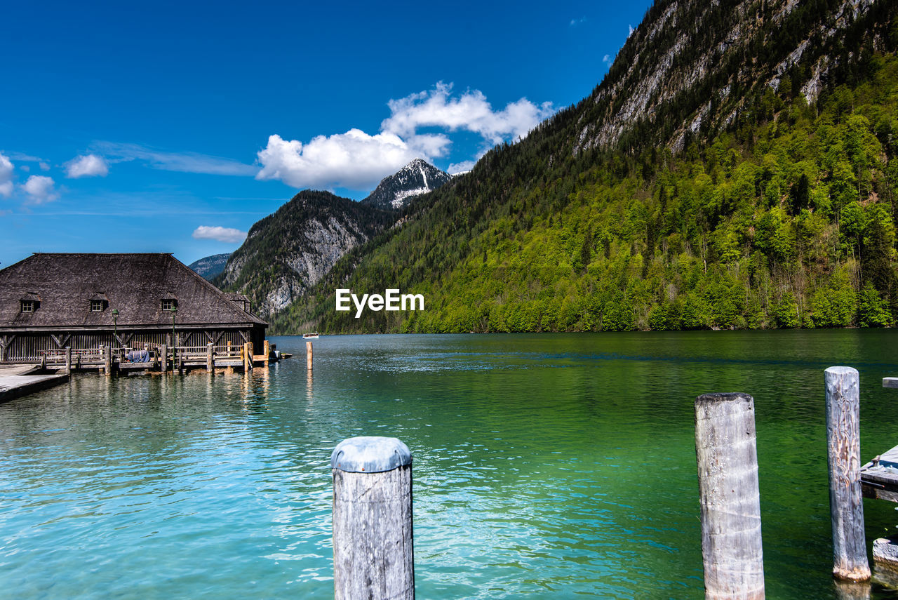 water, mountain, sky, scenics - nature, beauty in nature, nature, tranquil scene, cloud - sky, built structure, tranquility, wood - material, architecture, lake, no people, day, waterfront, non-urban scene, idyllic, blue, mountain range, outdoors, wooden post, turquoise colored