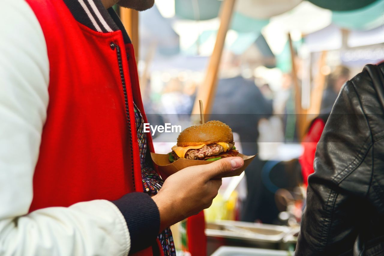Midsection Of Man Holding Burger