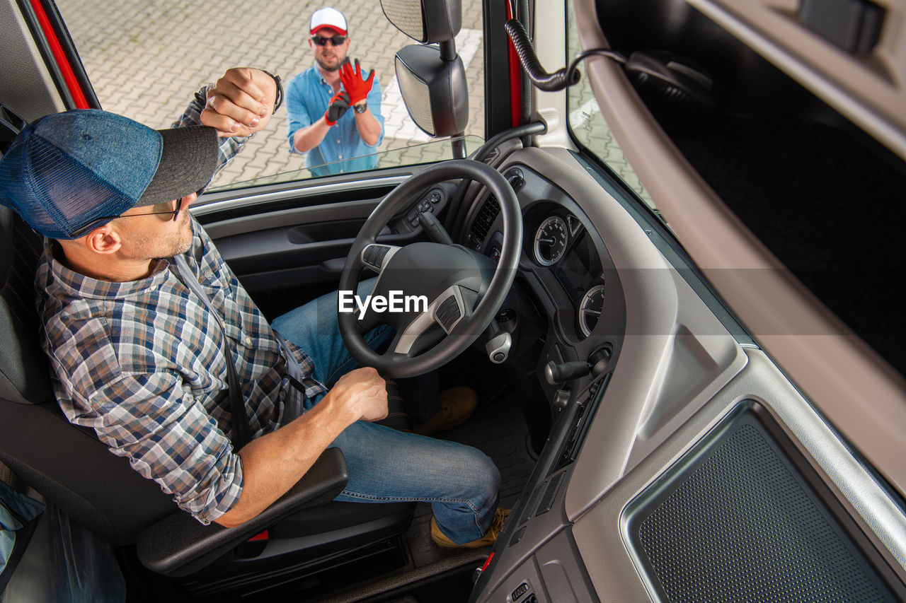 High angle view of truck driver sitting in truck