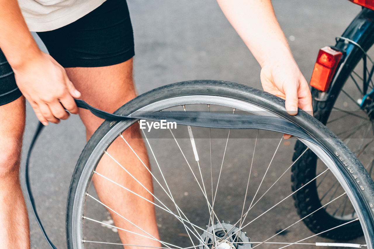 Cropped Image Of Man Repairing Flat Tire Of Bicycle On Street