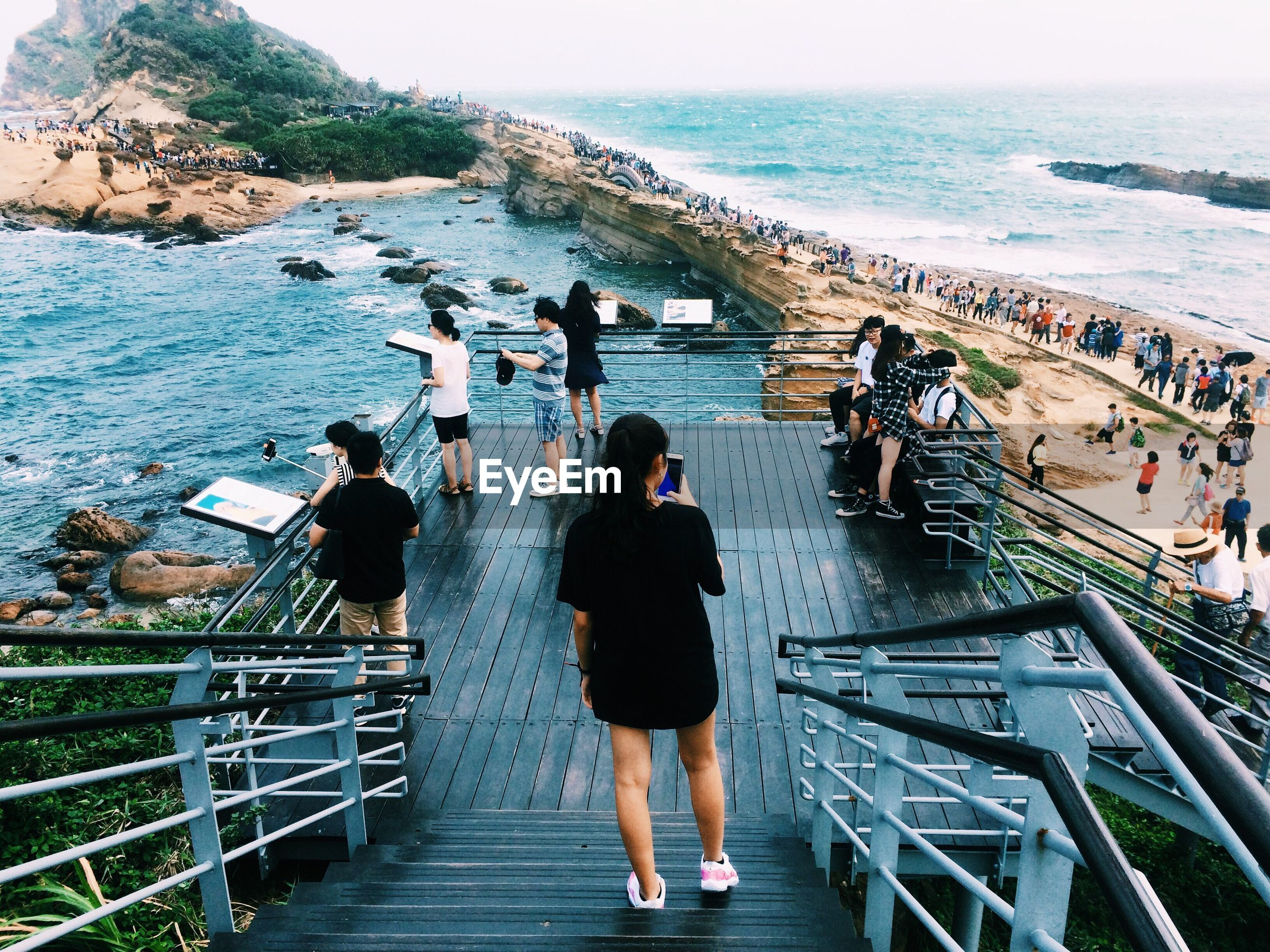 sea, real people, water, railing, lifestyles, horizon over water, high angle view, leisure activity, large group of people, women, day, rear view, men, standing, steps, nature, outdoors, full length, scenics, vacations, beauty in nature, technology, sky, people