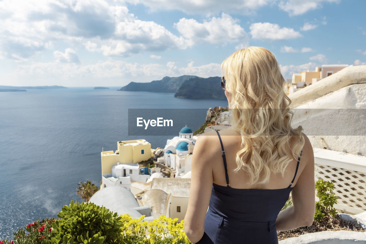 REAR VIEW OF WOMAN LOOKING AT SEA BY BUILDINGS AGAINST SKY