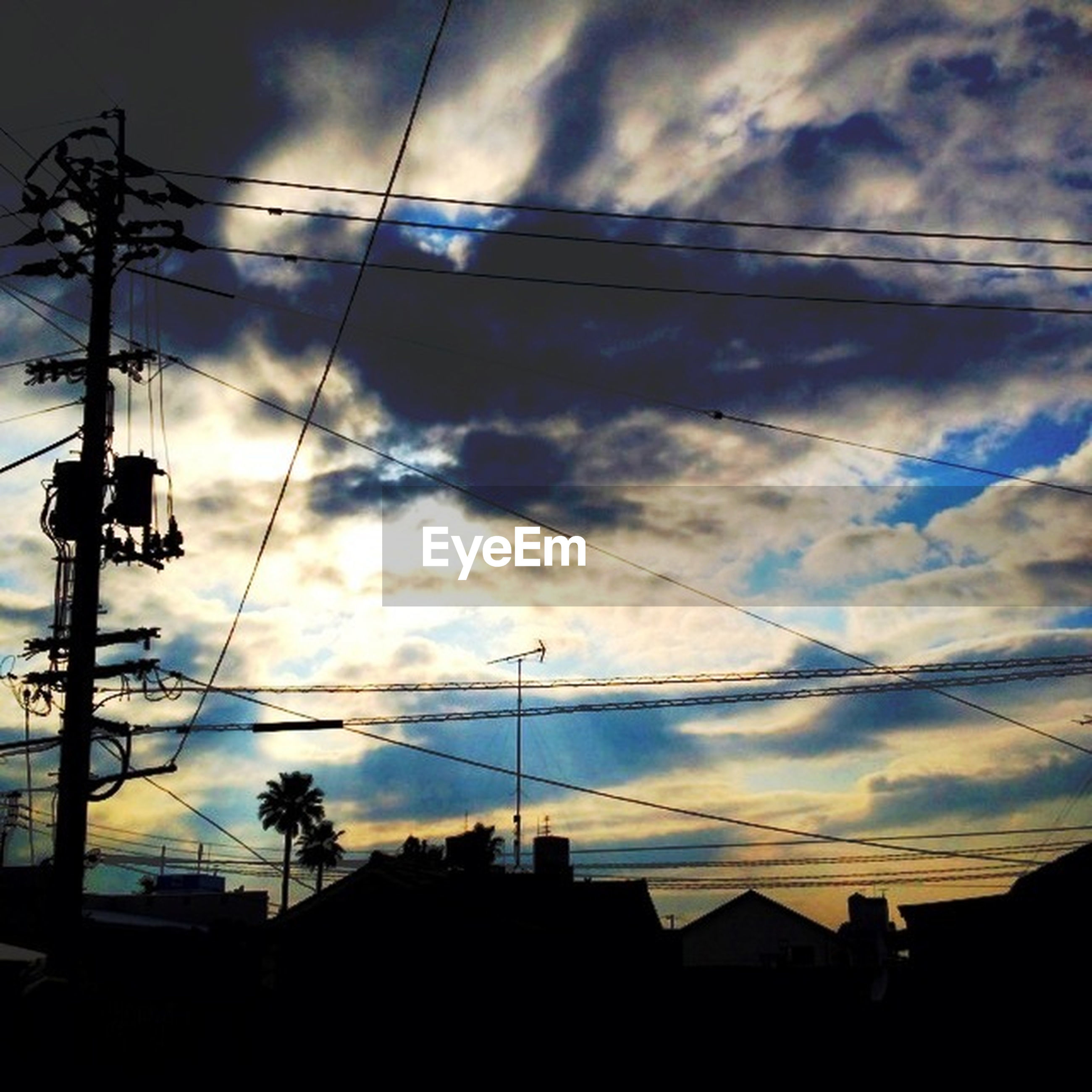power line, sky, electricity pylon, cable, building exterior, electricity, low angle view, silhouette, power supply, architecture, cloud - sky, built structure, sunset, cloudy, power cable, connection, cloud, house, residential structure, residential building