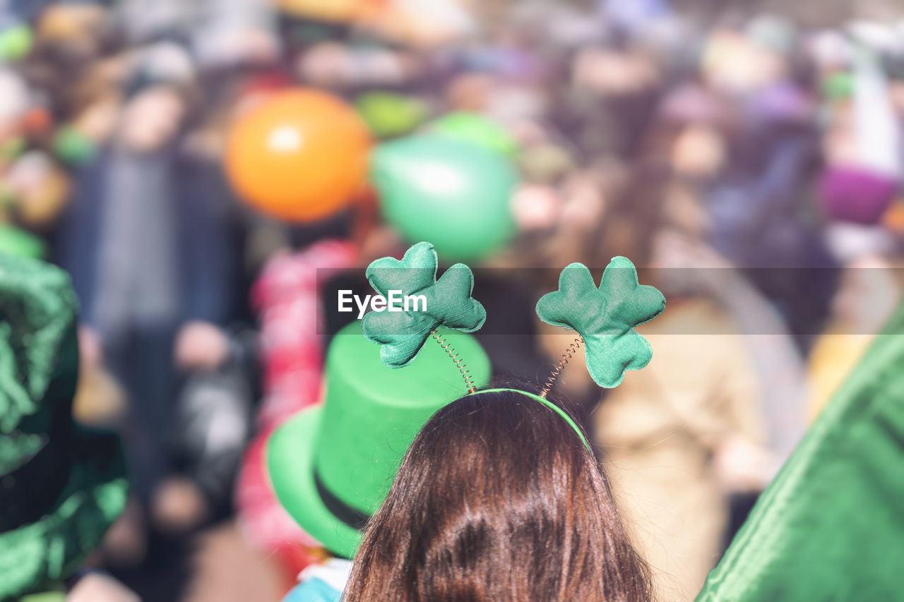 green color, real people, lifestyles, focus on foreground, rear view, people, women, headshot, day, multi colored, portrait, leisure activity, adult, close-up, group of people, celebration, outdoors, child, childhood, hairstyle, human hair