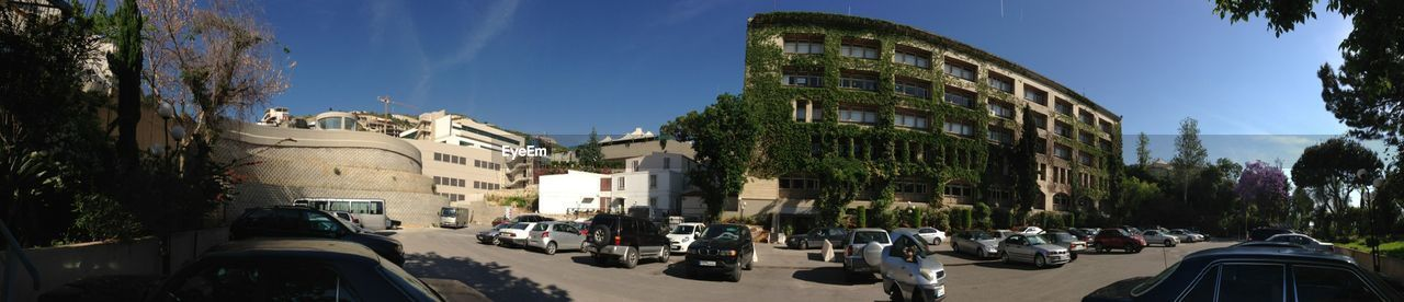 architecture, car, built structure, building exterior, tree, land vehicle, transportation, street, city, day, large group of people, panoramic, outdoors, fish-eye lens, sky, people