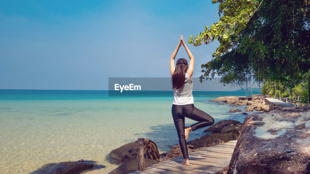 Rear view of woman doing yoga by sea against sky