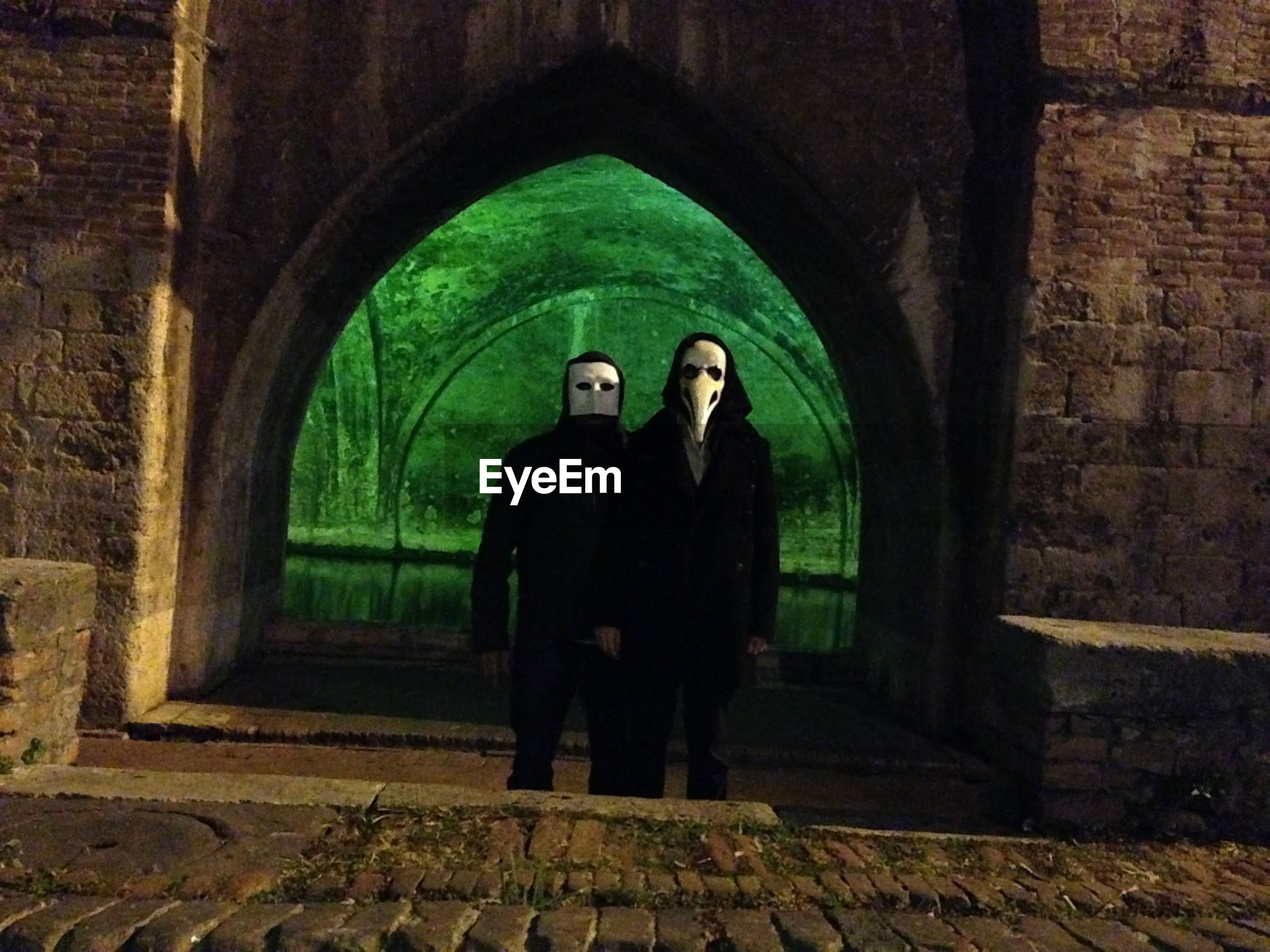 Man and woman wearing masks standing at entrance of historic building