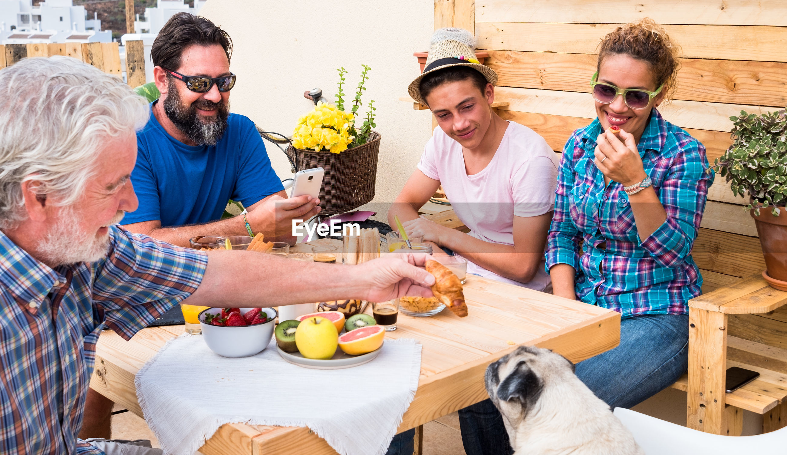 Happy family feeding pug during breakfast at building terrace