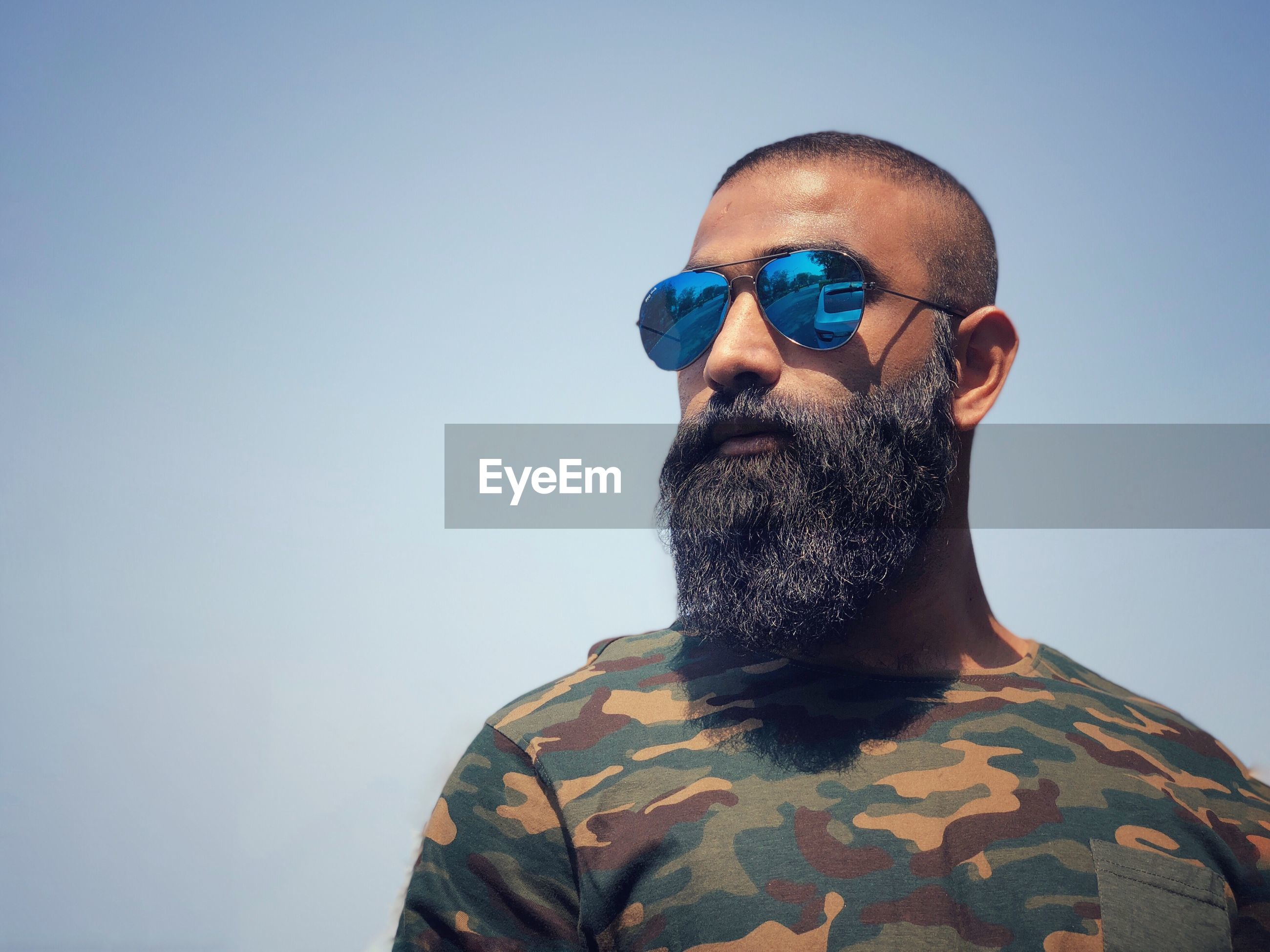 Close-up of bearded man wearing sunglasses against clear sky