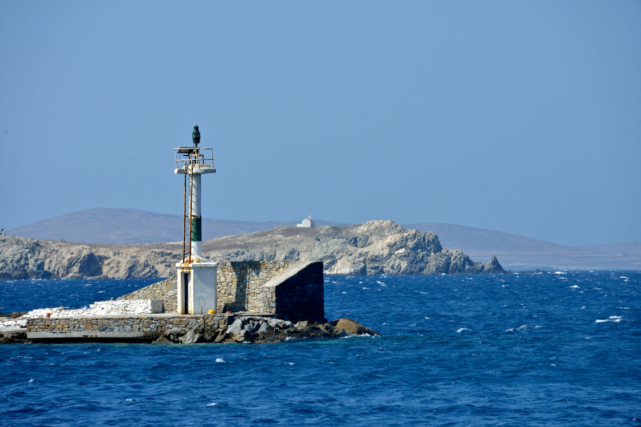 water, sky, sea, clear sky, architecture, beauty in nature, built structure, scenics - nature, blue, nature, waterfront, mountain, tower, no people, day, guidance, building, copy space, building exterior, lighthouse, outdoors