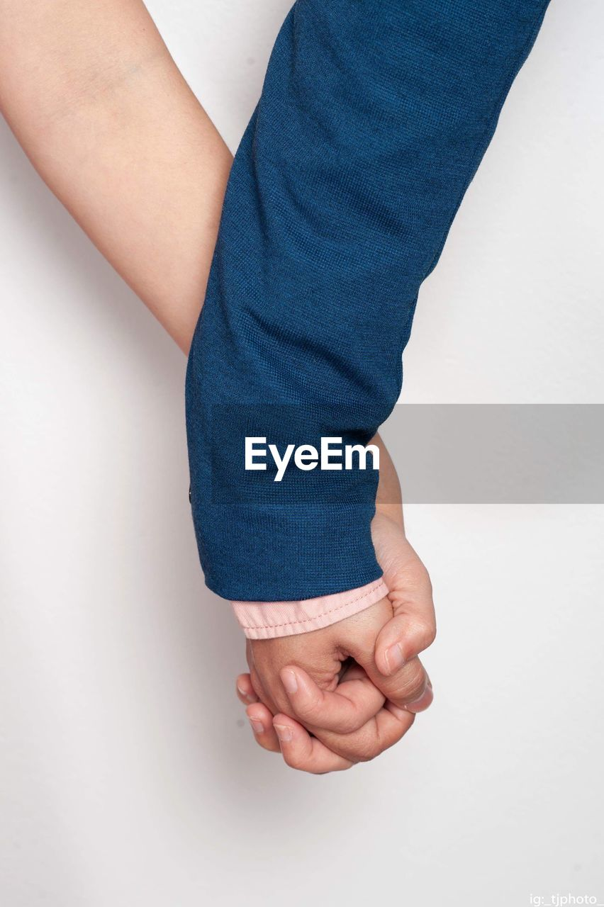 Cropped image of couple holding hands over white background