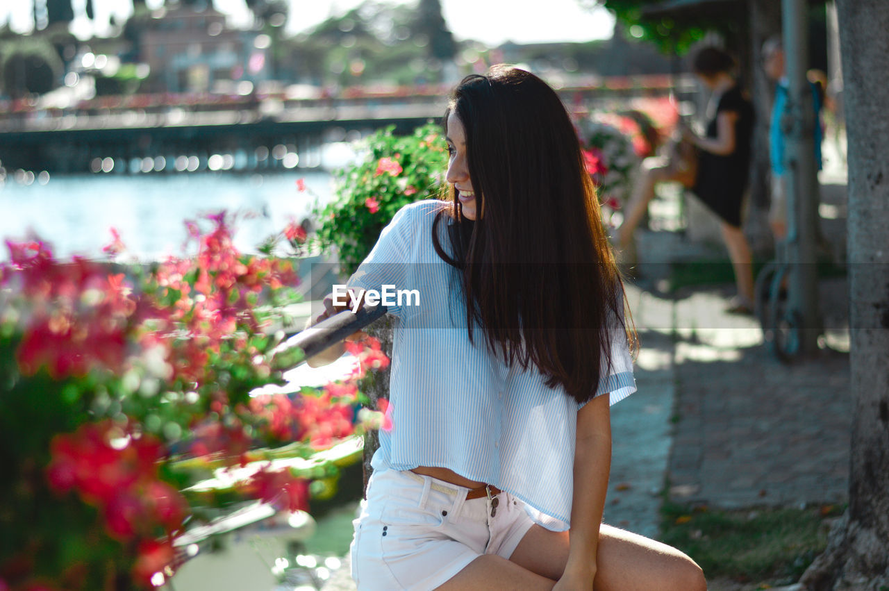 Smiling young woman looking away while sitting by plants in park