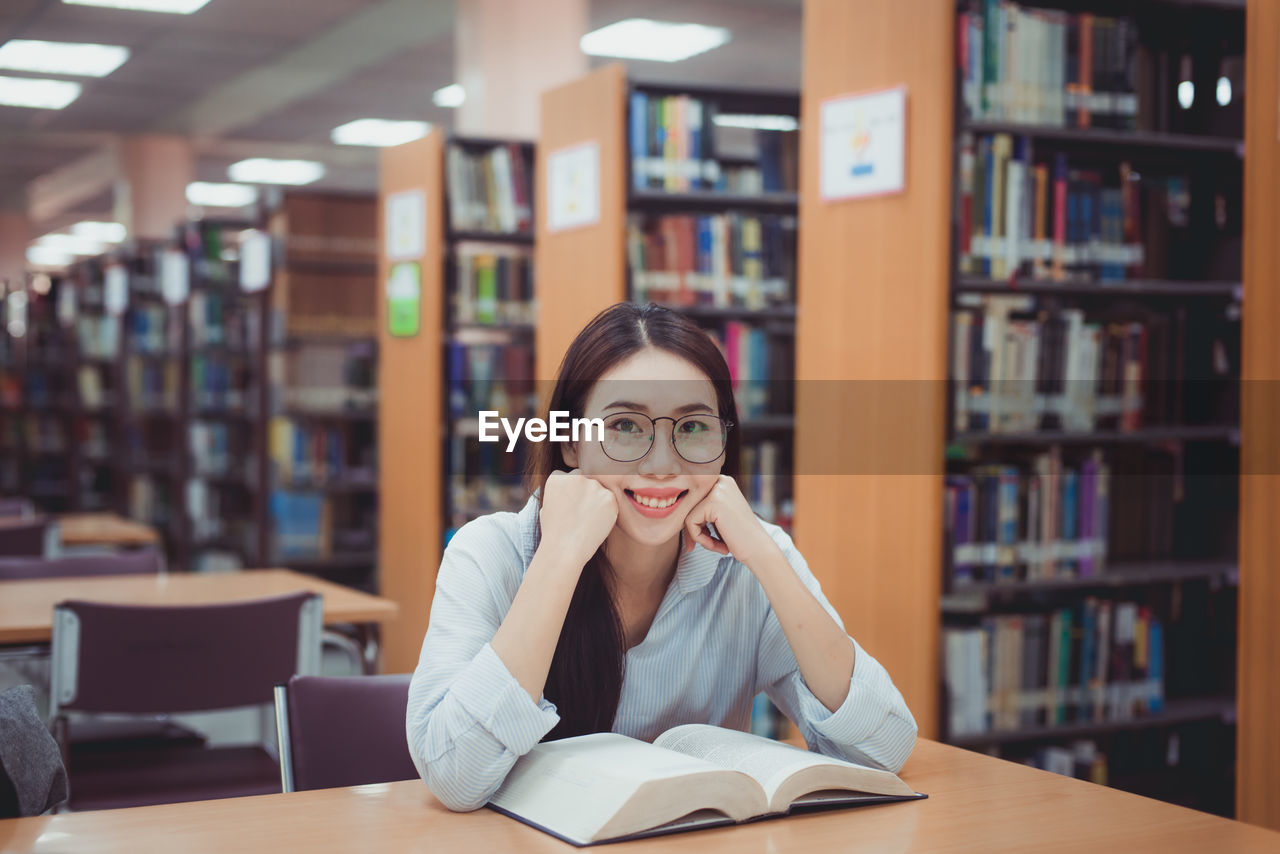 Portrait Of Woman Reading Book While Sitting In Library