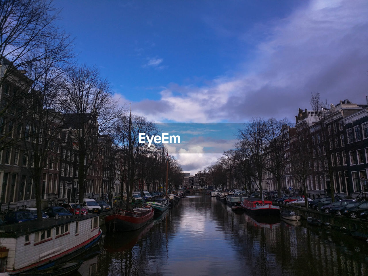 canal, sky, nautical vessel, bare tree, architecture, built structure, transportation, mode of transport, building exterior, water, in a row, moored, day, outdoors, reflection, cloud - sky, tree, travel destinations, waterfront, no people, city, nature