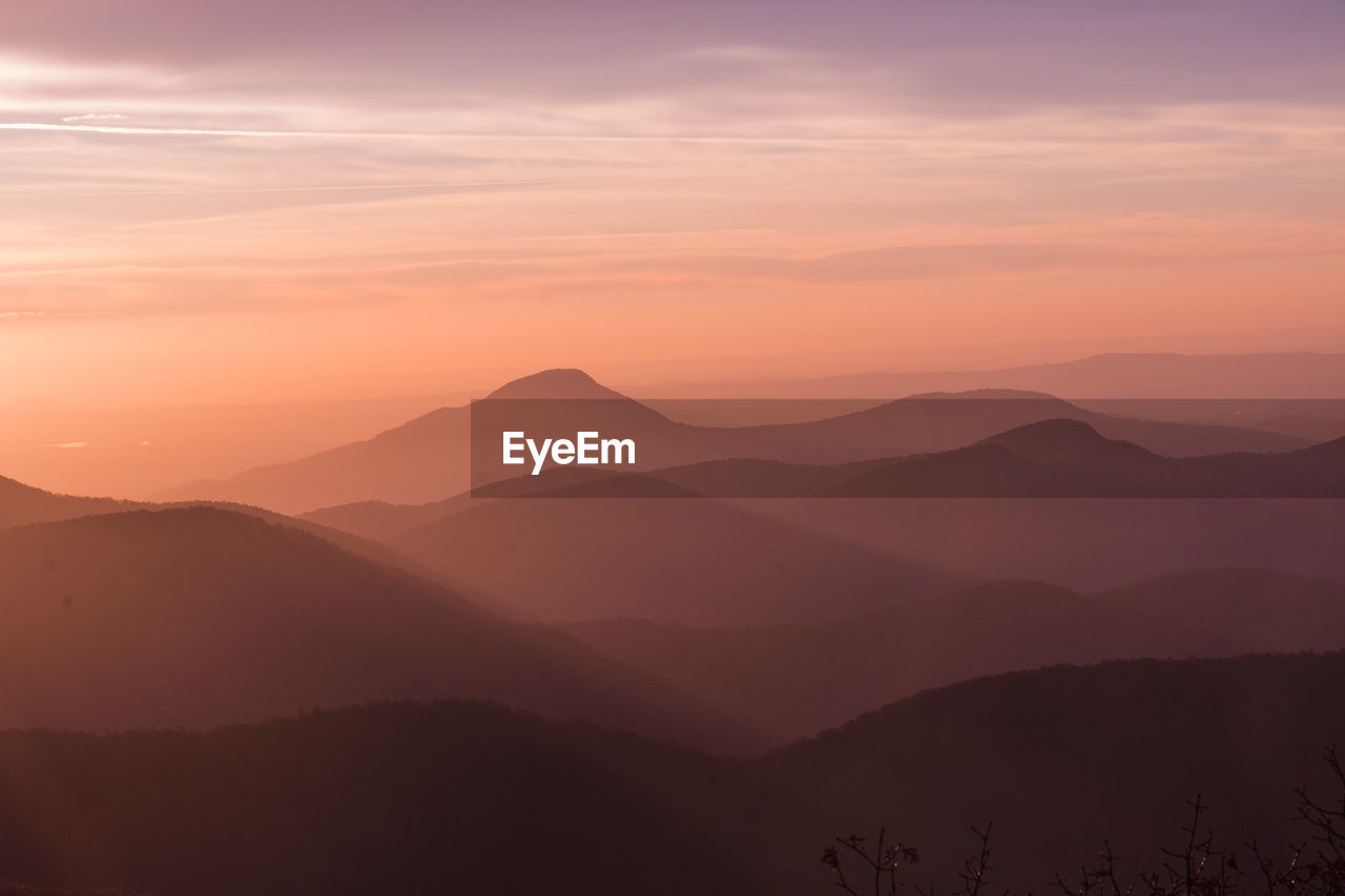 Scenic View Of Mountain Range Against Sky At Sunset