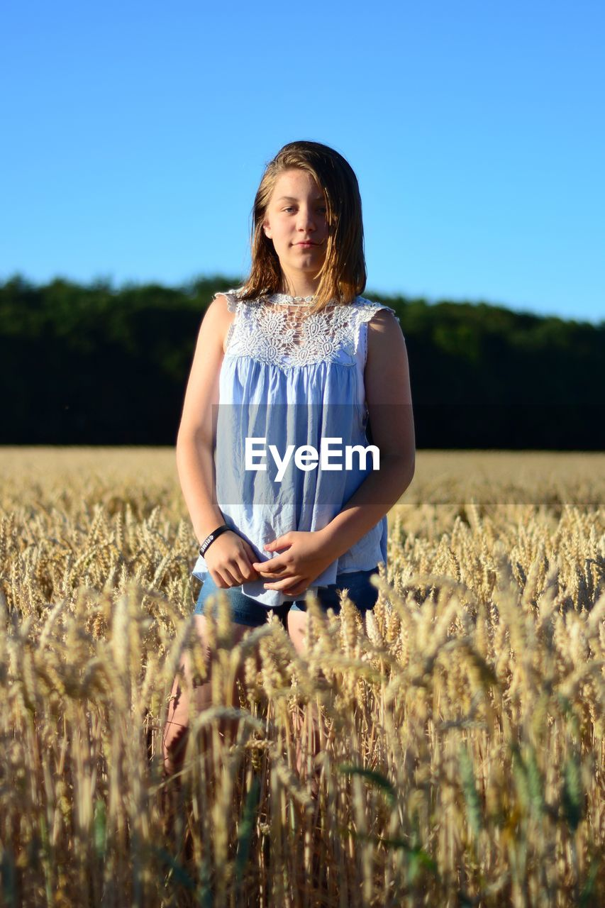 Portrait Of Teenage Girl Standing At Farm Against Clear Blue Sky