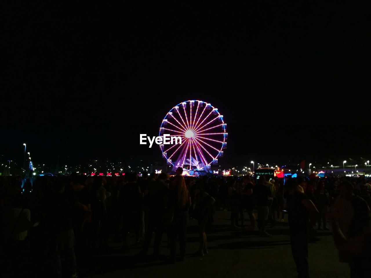 illuminated, night, large group of people, arts culture and entertainment, real people, leisure activity, amusement park, enjoyment, men, women, outdoors, amusement park ride, crowd, sky, nature, people