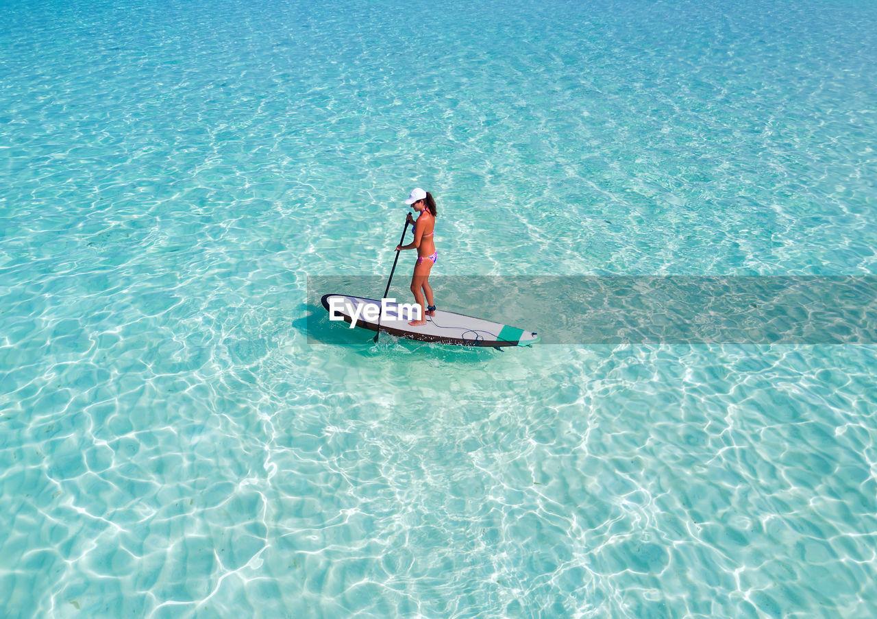 Woman Paddleboarding In Sea