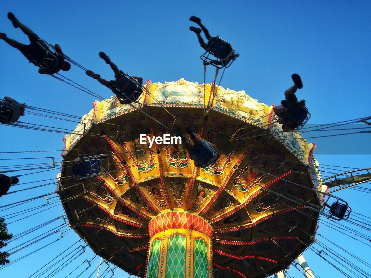 Low angle view of chain swing ride in amusement park