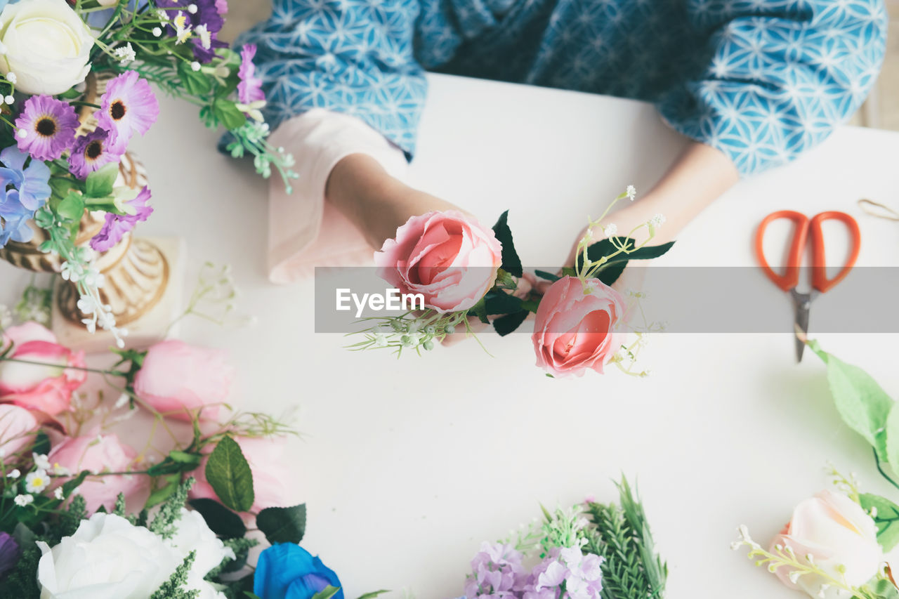 Close-up of woman hands making flower bouquet over table