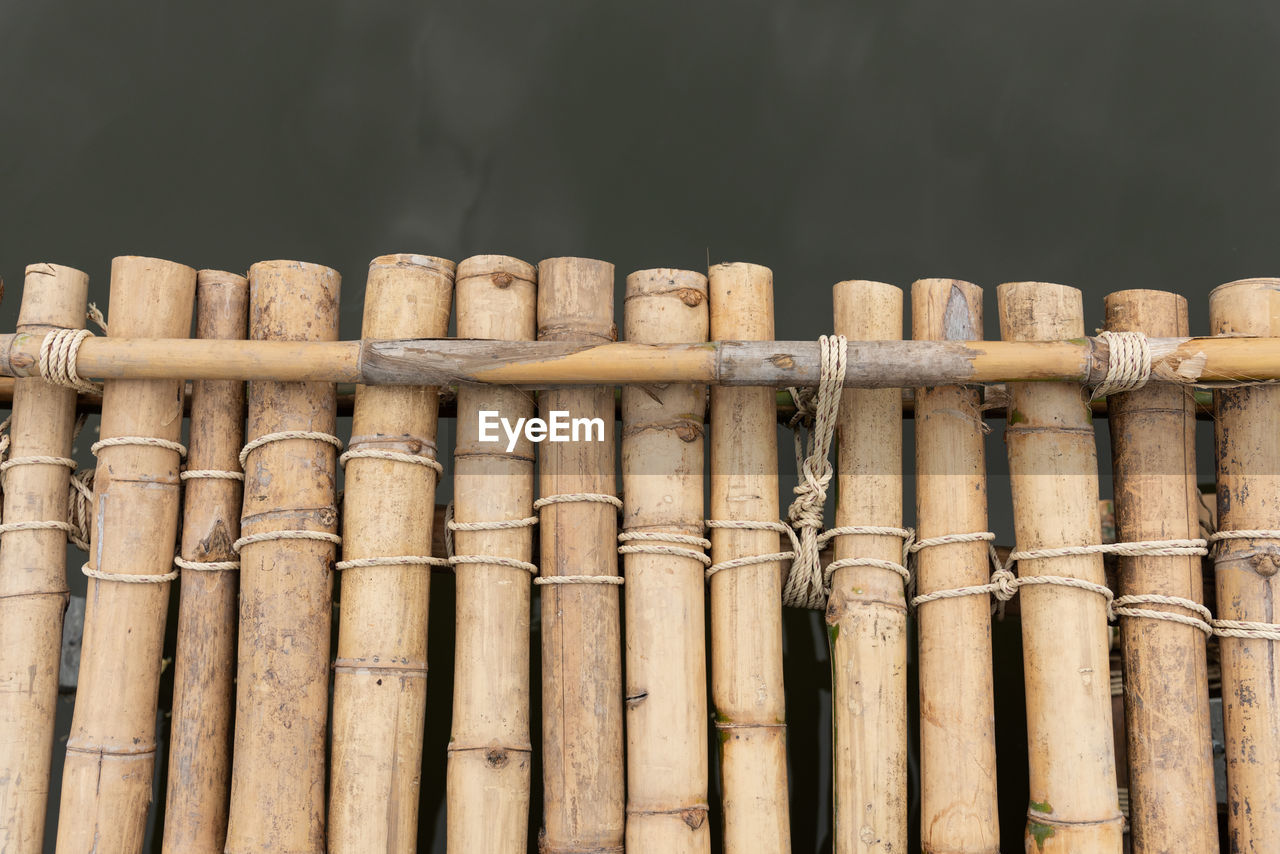 wood - material, no people, bamboo - material, large group of objects, bamboo, brown, side by side, close-up, pattern, day, nature, stack, focus on foreground, abundance, outdoors, in a row, still life, bamboo - plant, low angle view, sunlight