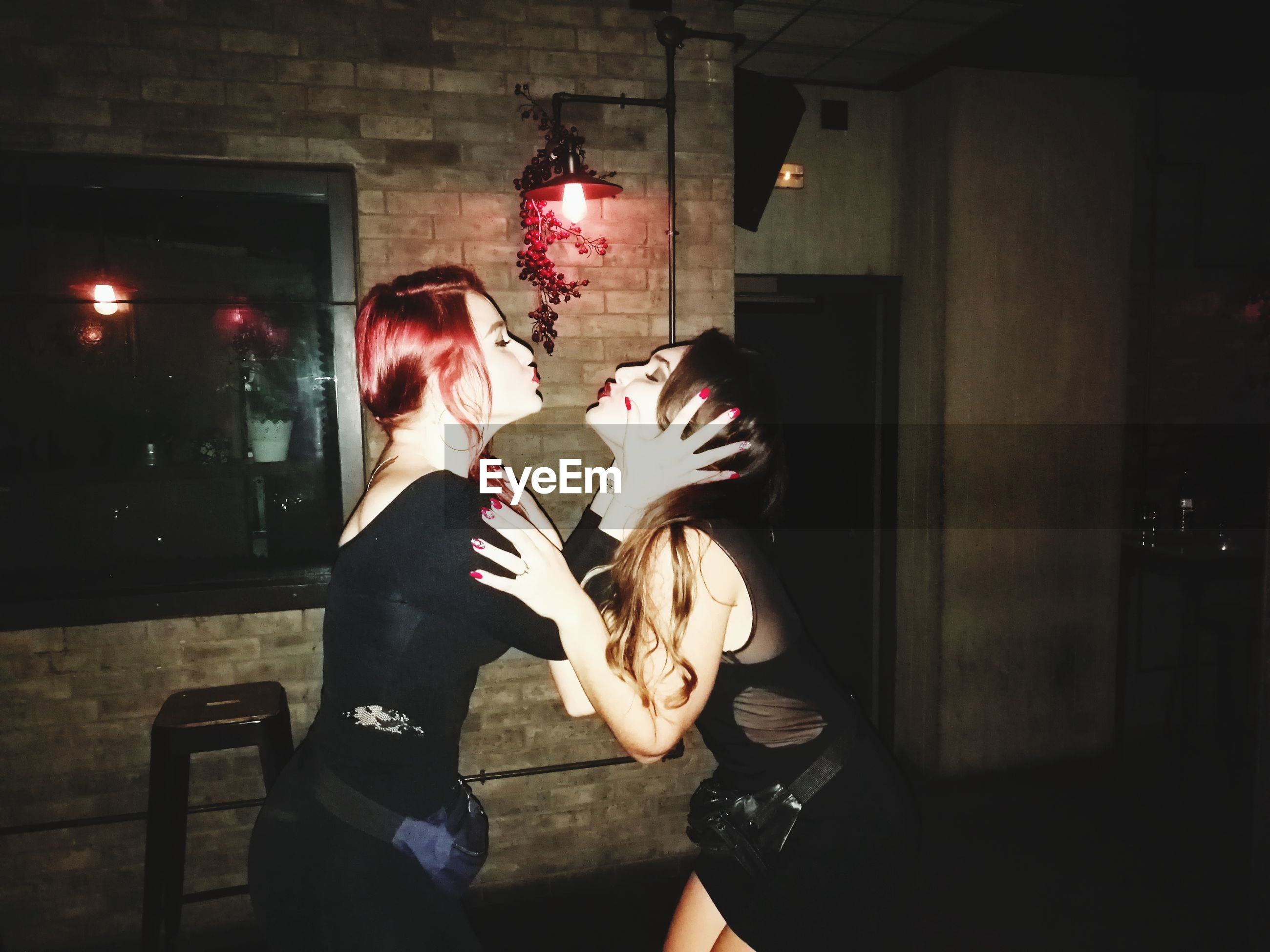 real people, indoors, two people, love, celebration, illuminated, togetherness, men, lifestyles, young women, standing, young adult, women, night, human hand, people