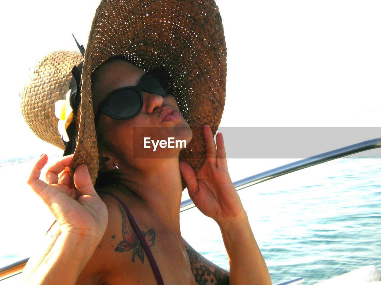 Young woman wearing hat while pouting in cruise ship by sea against sky