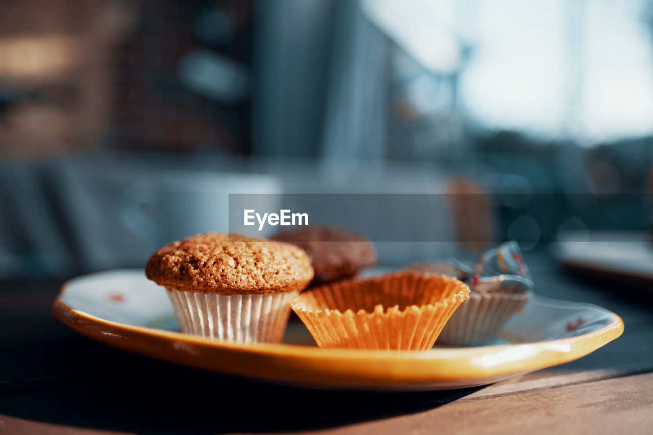 sweet food, food, food and drink, ready-to-eat, dessert, sweet, cupcake, cake, table, baked, indulgence, freshness, unhealthy eating, temptation, plate, focus on foreground, indoors, close-up, still life, no people, cupcake holder, muffin, snack
