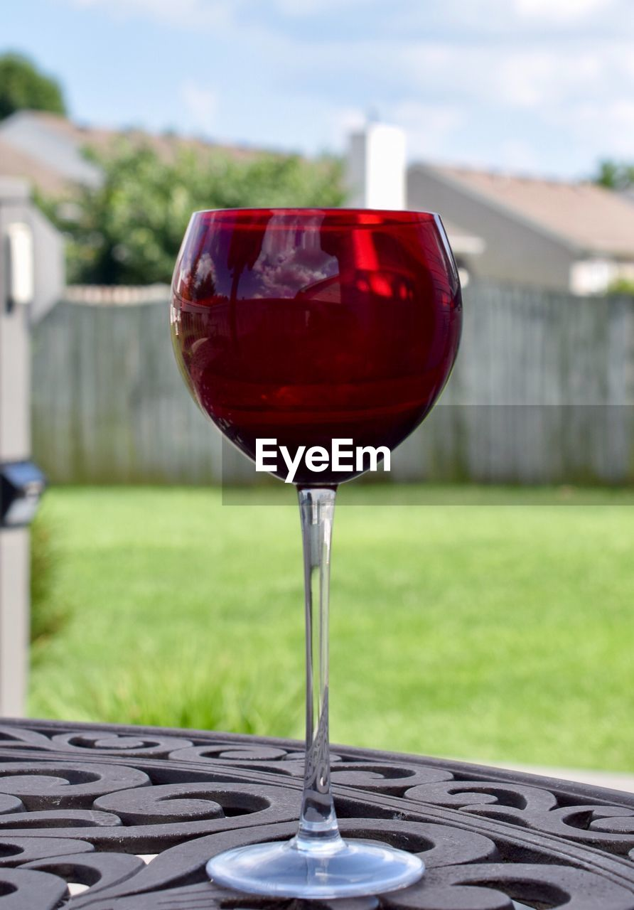focus on foreground, red, wineglass, no people, food and drink, table, outdoors, drink, refreshment, day, alcohol, drinking glass, freshness, close-up, sky