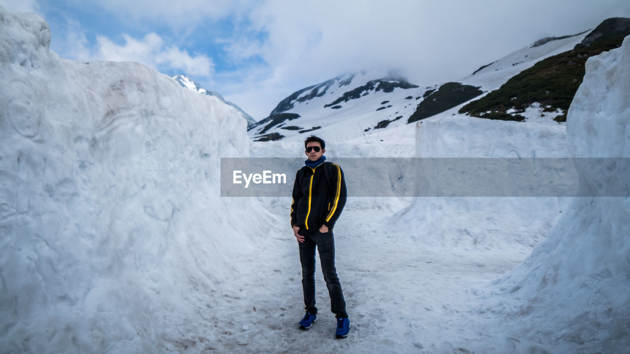 Full Length Of Young Man Standing Amidst Snow Covered Rocks