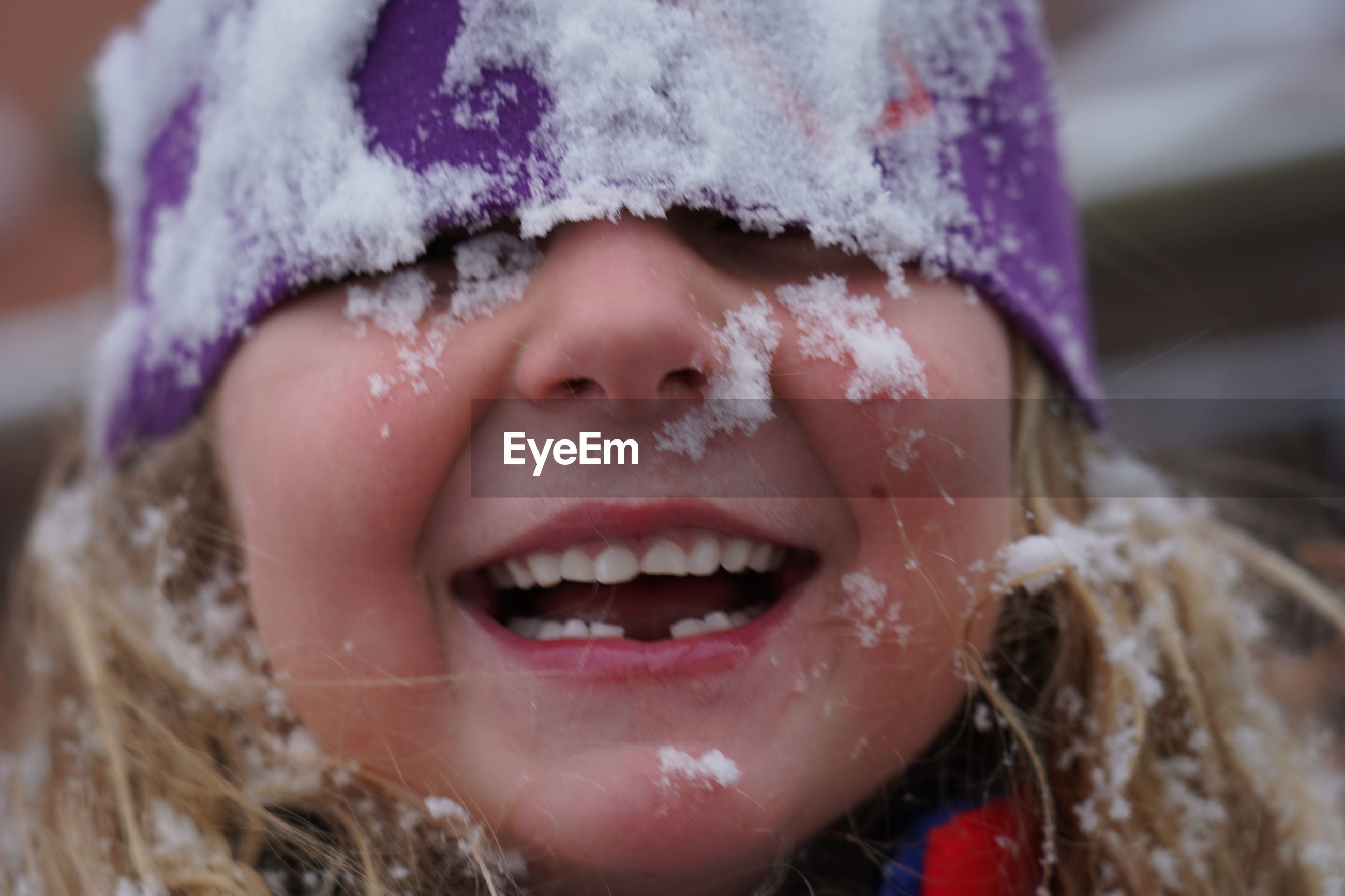 Close-up of cute smiling girl with snow on face