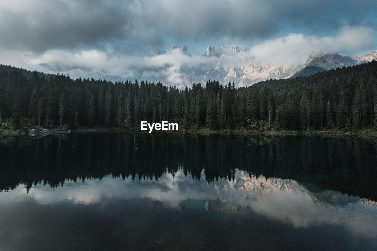 Scenic image of fairytale lake during sunrise with azure mountain lake carezza, dolomites, italy
