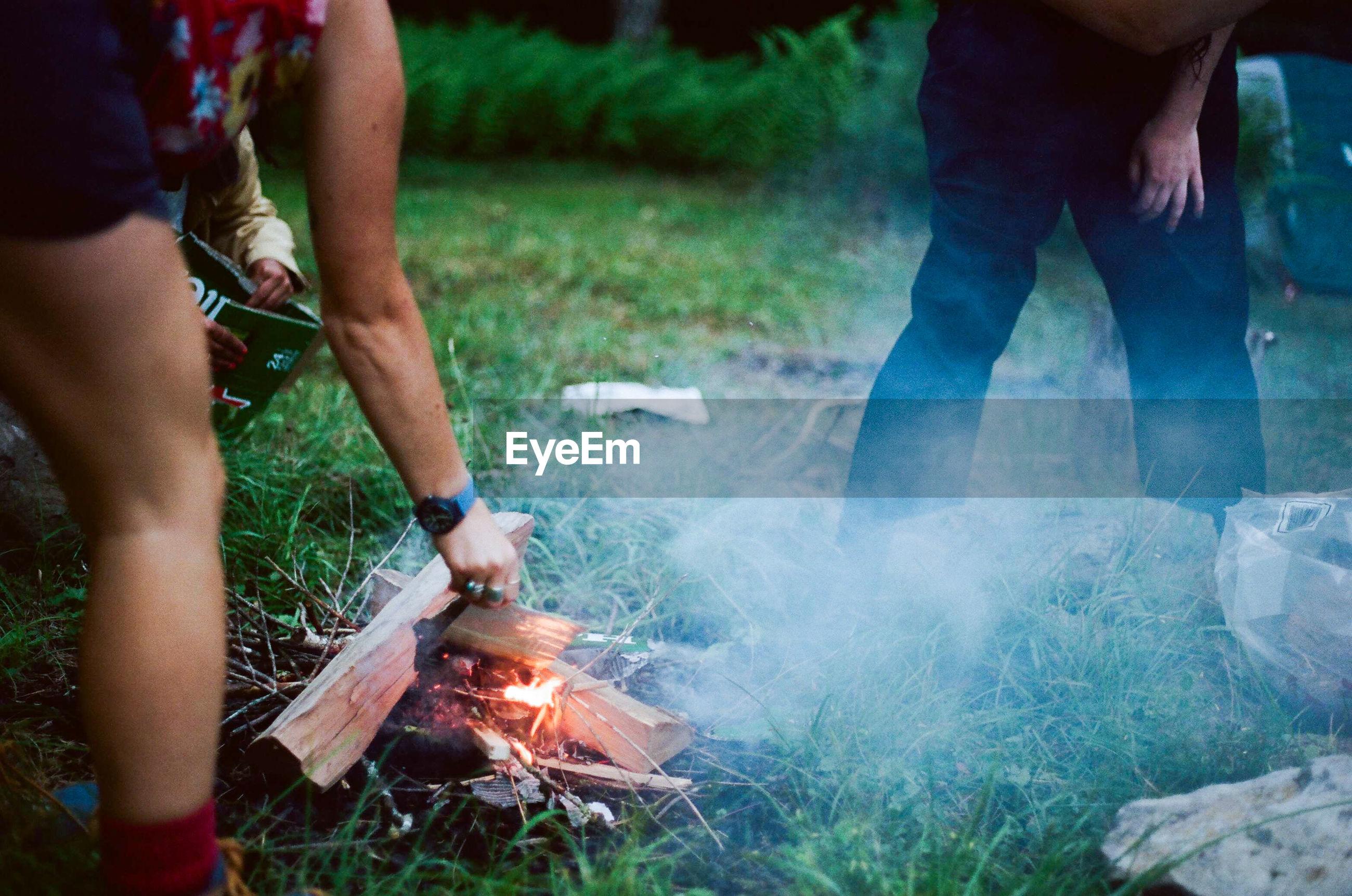 Friends making campfire on grassy field