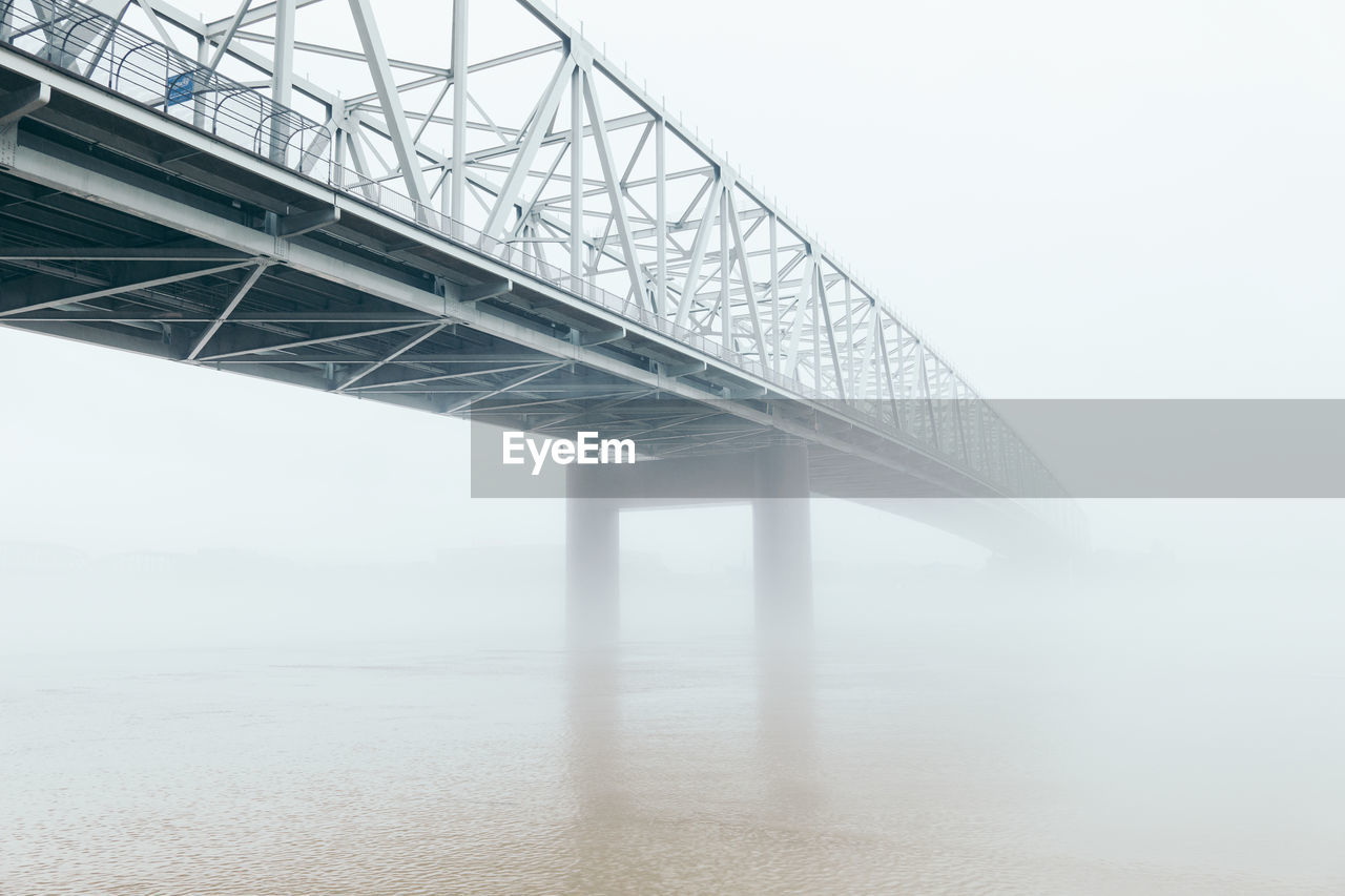 built structure, connection, bridge, architecture, transportation, bridge - man made structure, fog, engineering, sky, nature, day, low angle view, water, outdoors, metal, sea, architectural column, steel, alloy
