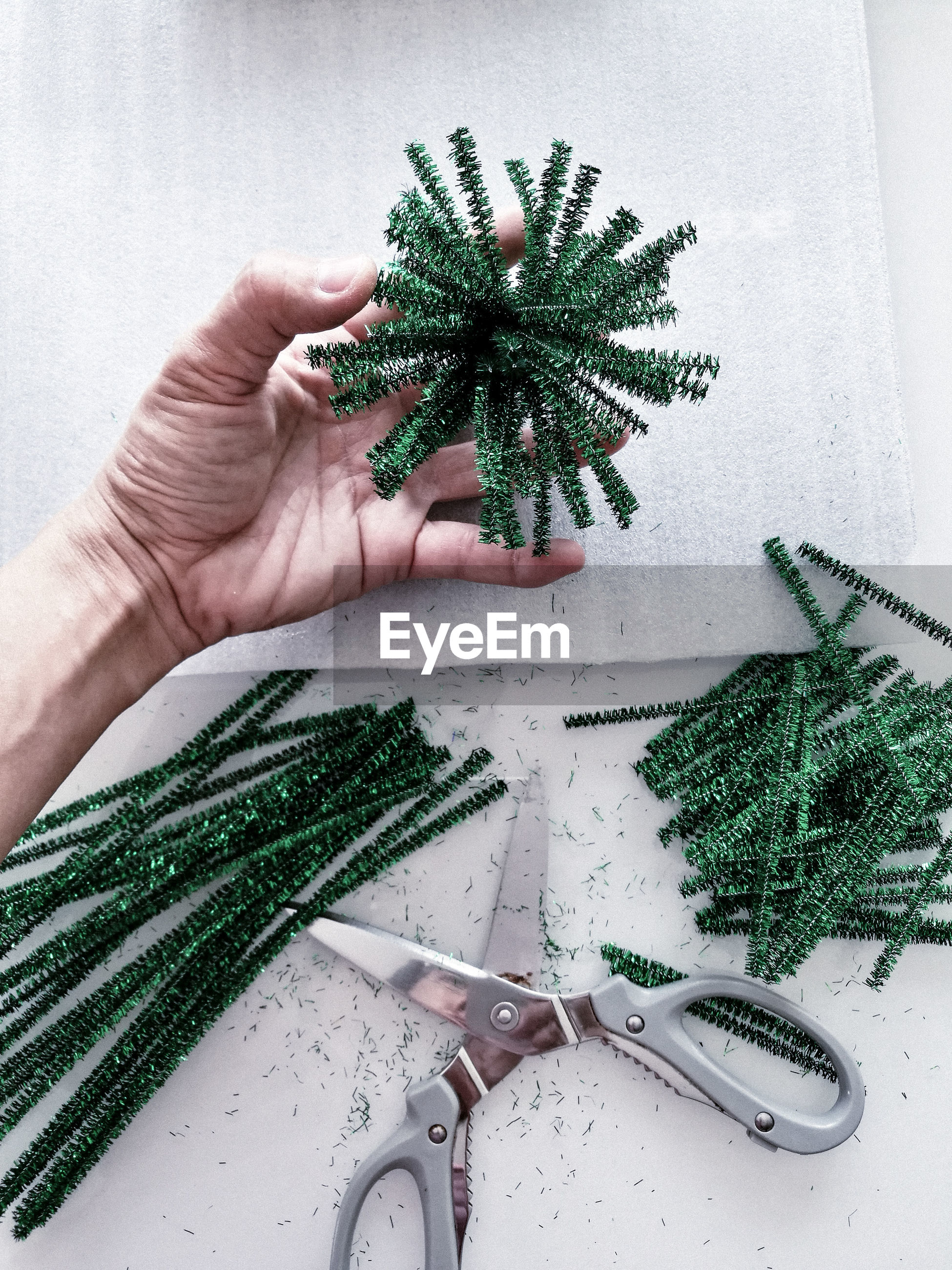 Cropped hand of woman holding green decoration at home