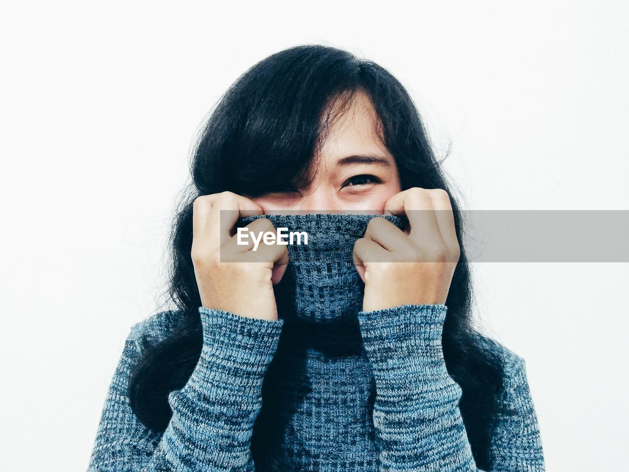 Portrait Of Woman Covering Face With Turtleneck T-Shirt Over White Background