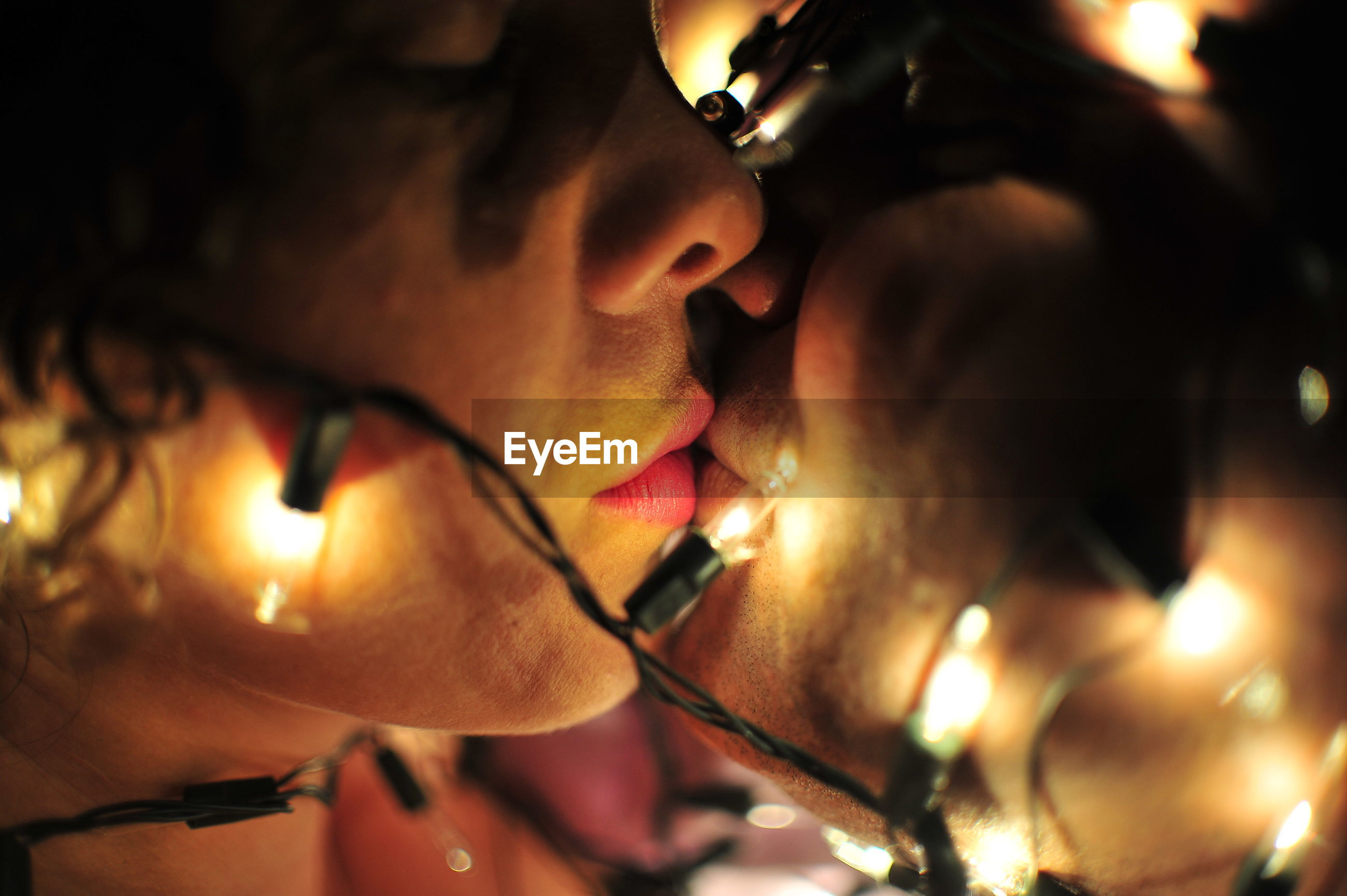 Close-up of young couple with illuminated string lights kissing in darkroom