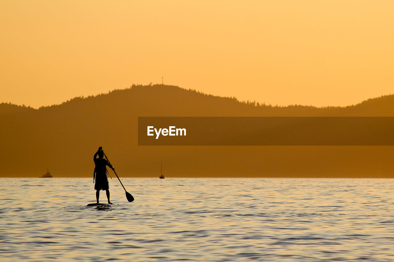 Rear View Of Man Paddleboarding At Lake Against Sky During Sunset