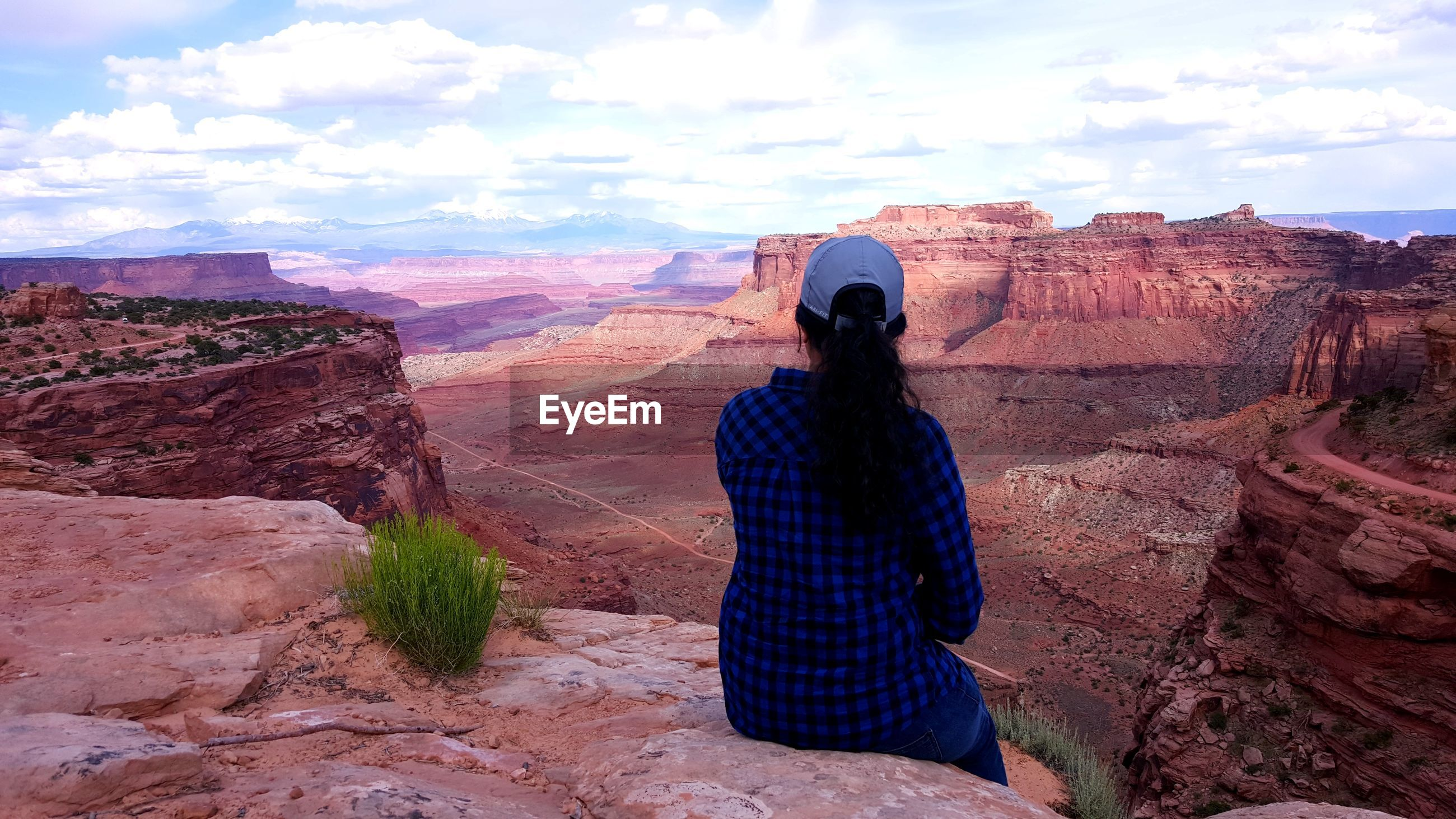 Rear view of woman sitting against canyons in utah