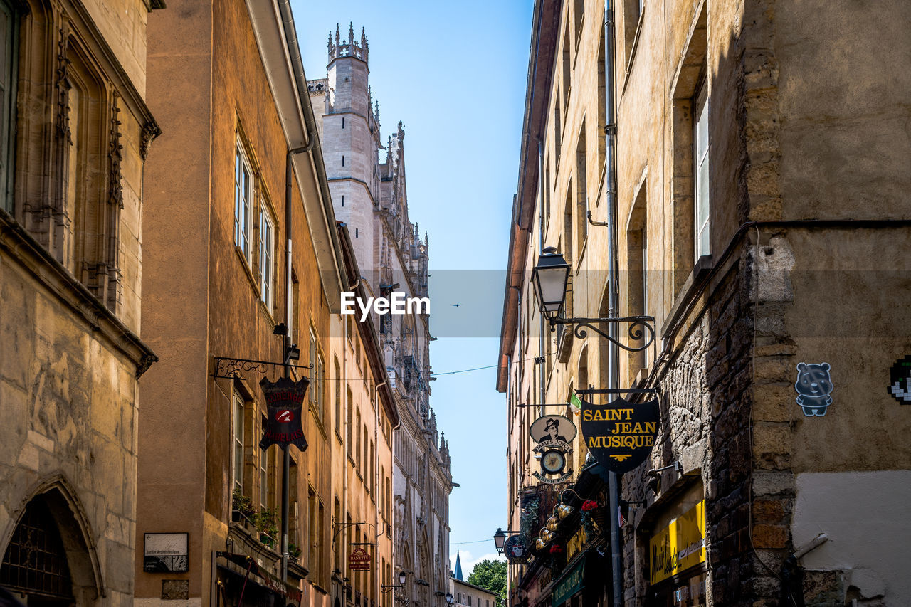 building exterior, built structure, architecture, building, city, sky, day, residential district, clear sky, nature, low angle view, window, incidental people, lighting equipment, street, outdoors, sign, sunlight, communication, alley