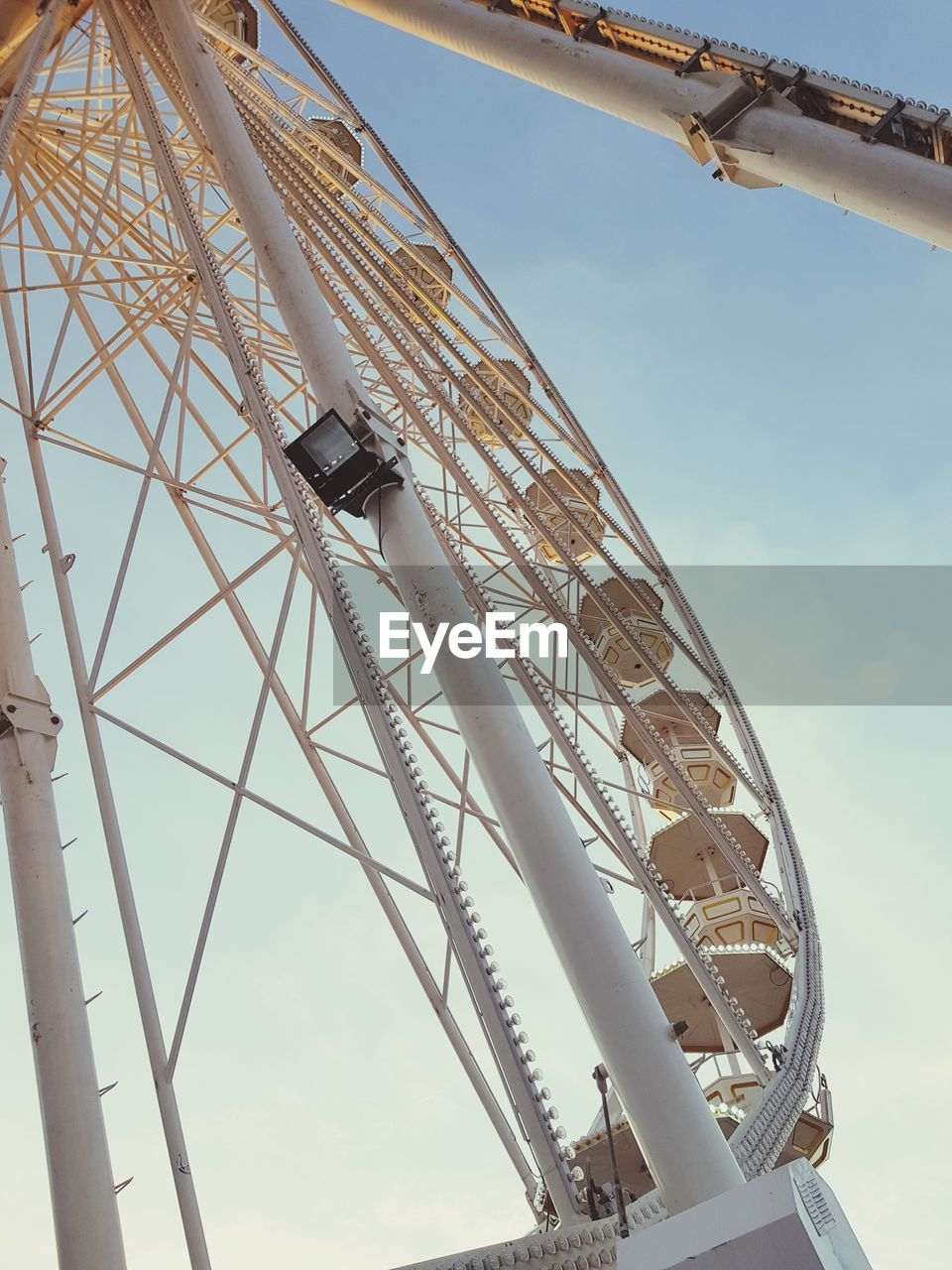 low angle view, sky, built structure, architecture, day, metal, no people, nature, amusement park, amusement park ride, ferris wheel, arts culture and entertainment, outdoors, cloud - sky, building exterior, tall - high, machinery, crane - construction machinery, construction industry, focus on foreground, fairground