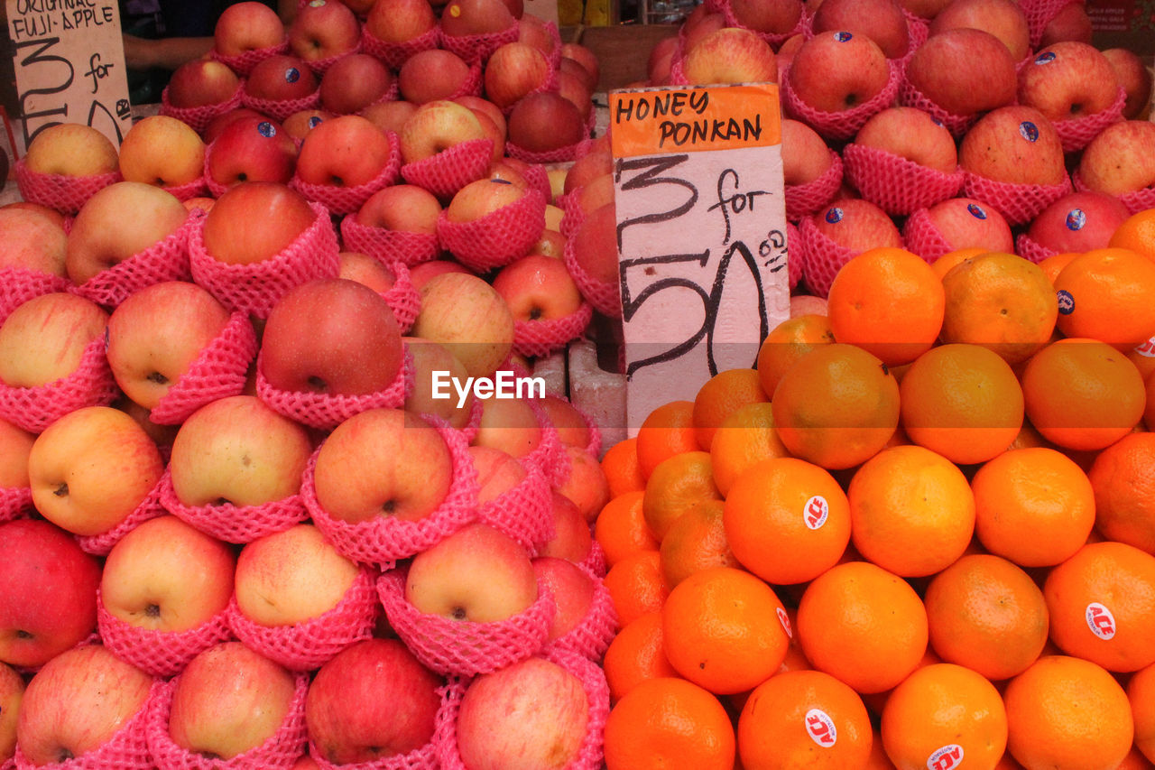 food and drink, healthy eating, fruit, food, market, freshness, retail, wellbeing, abundance, large group of objects, orange color, for sale, market stall, price tag, citrus fruit, choice, text, orange, communication, apple - fruit, no people, sale, ripe, retail display
