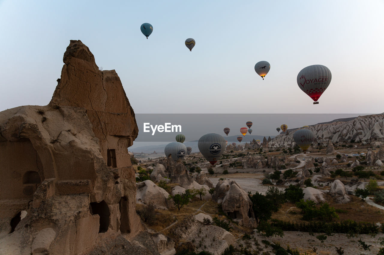 HOT AIR BALLOONS FLYING OVER ROCK FORMATION