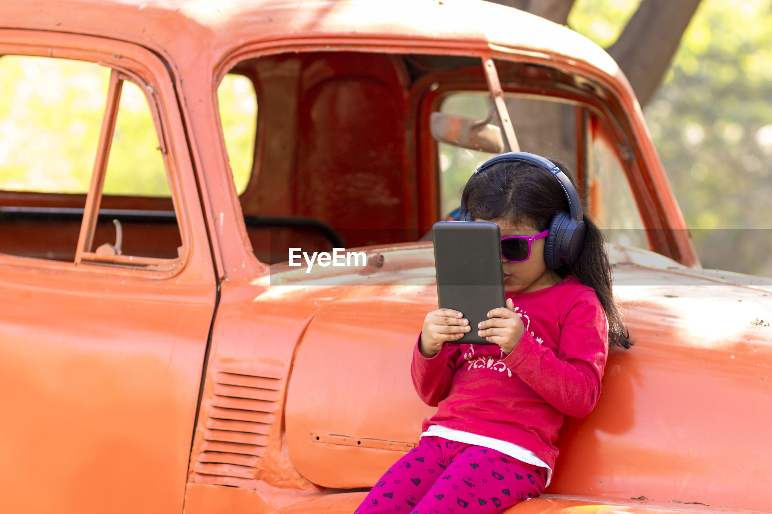 Girl using digital tablet and listening to music while leaning against abandoned car