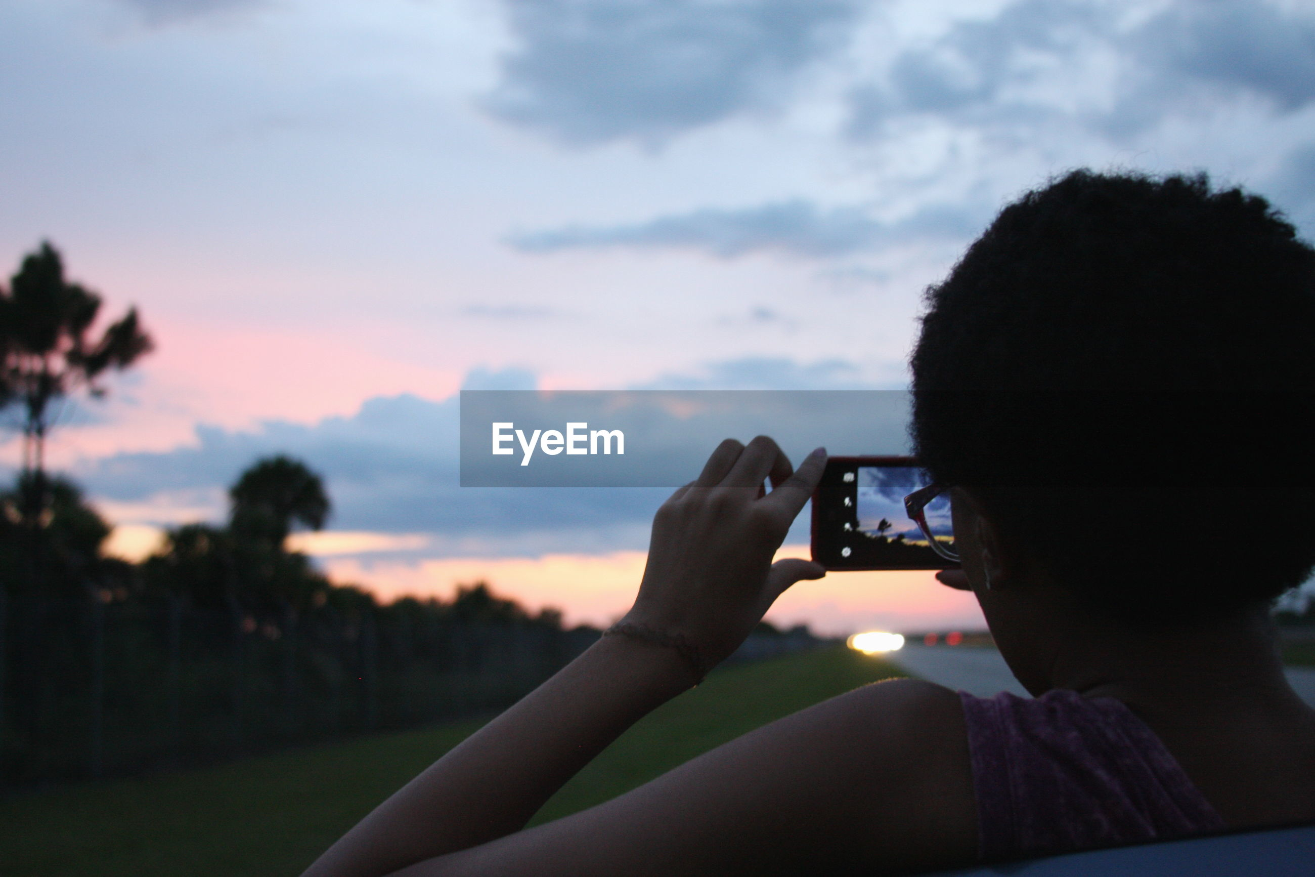 Rear view of woman photographing sky during sunset on field