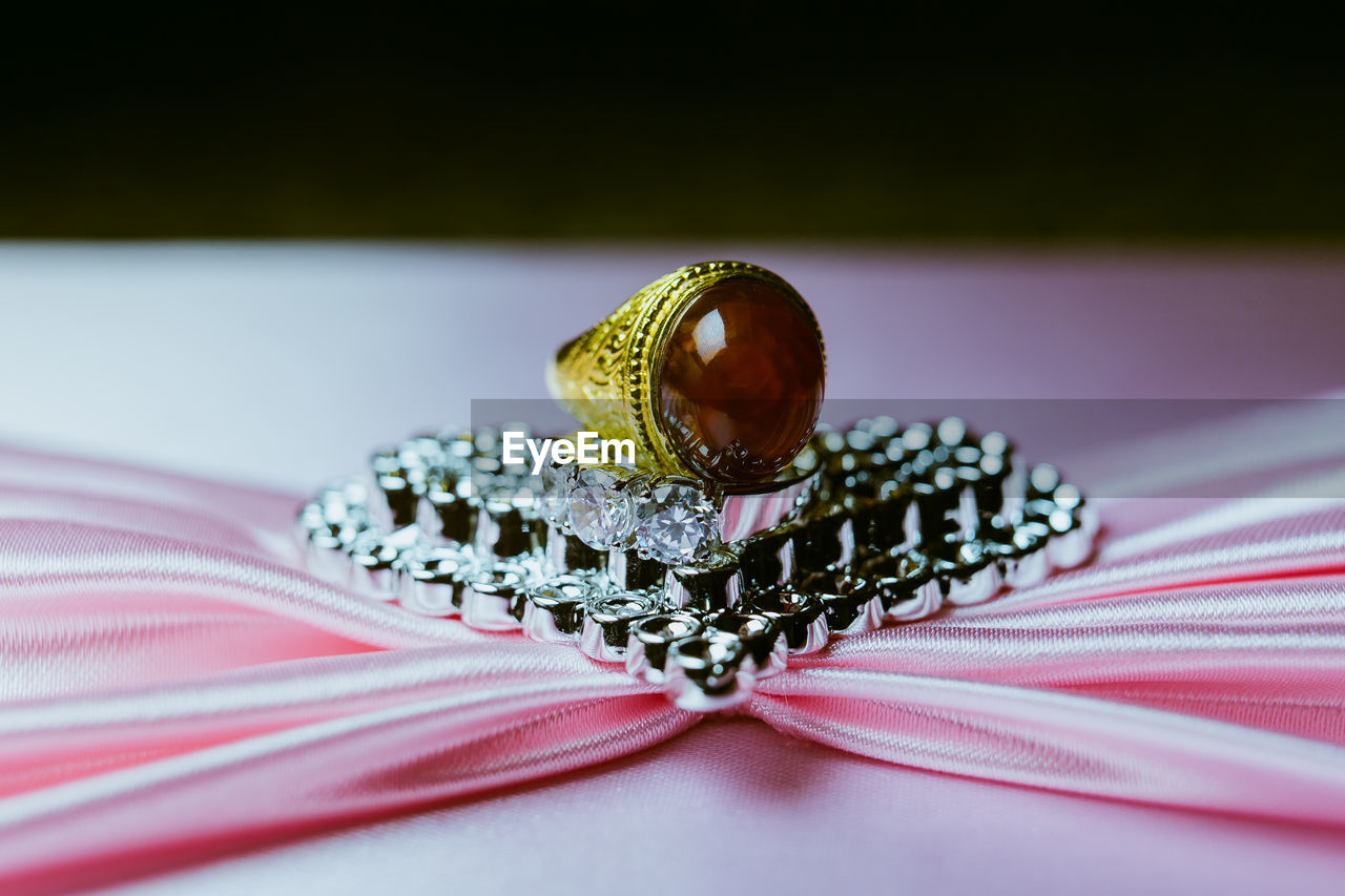 jewelry, close-up, ring, still life, selective focus, diamond - gemstone, no people, indoors, wealth, wedding ring, table, luxury, gemstone, focus on foreground, two objects, pattern, wedding, pink color, life events, textile, personal accessory, expense